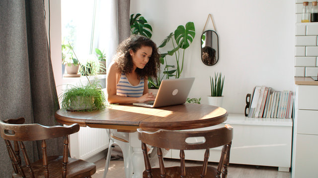 Charming young woman typing on laptop computer at home.