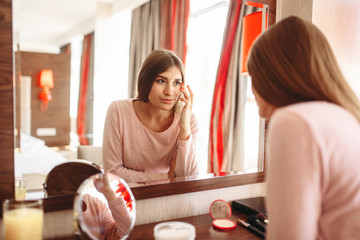 Young woman in pajama in front of the mirror