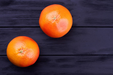 Two whole grapefruits and copy space. Organic grapefruits on dark wooden background with text space.
