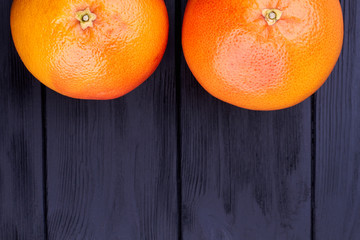 Two large grapefruits and text space. Fresh tropical fruits and copy space. Grapefruits and diet.