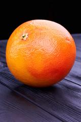 Whole fresh grapefruit on dark background. Big organic grapefruit on black wooden background, vertical image.