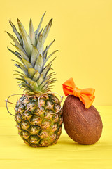 Composition from pineapple and coconut. Pineapple in eyeglasses and coconut with red bow on yellow background. Tropical vacation concept.