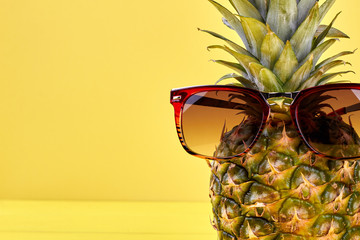 Close up pineapple in sunglasses and copy space. Fresh hawaiian pineapple wearing sunglasses on yellow background with text space.