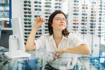 Female optician and consumer chooses glasses frame