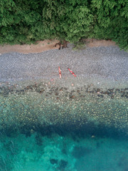 Aerial view of a beach near a forest with red canoes