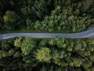 Asphalt road in forest from above with motorcycle