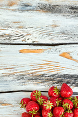 Heap of strawberries with copy space on top. Fresh ripe strawberries on old wooden boards. Taste of summer.