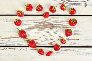Heart shape from fresh ripe strawberries. Delicious summer berries forming heart shape on vintage wooden surface.