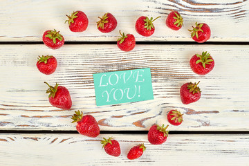 Heart shape made of ripe strawberries. Heart from juicy berries and color paper card with text for you. Romantic arrangement for Valentines Day.