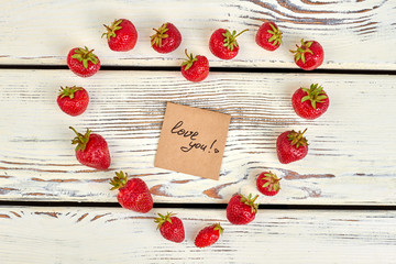 Valentines Day background. Shape of heart from strawberries on wooden background. Love and romance concept.
