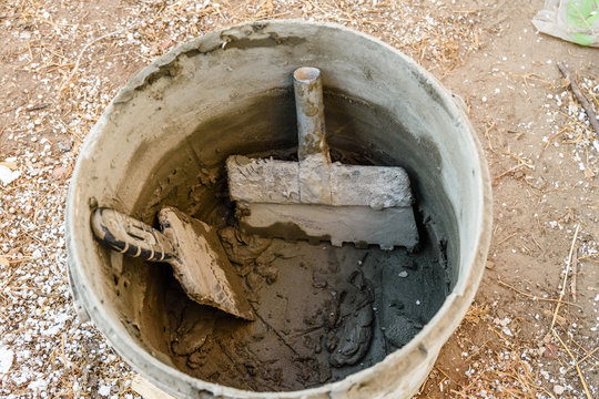 Two spatulas in bucket with the mortar