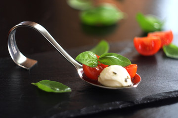 Spoed Foto op Canvas Voorgerecht Appetizers with mozzarella and tomato on spoon - selective focus