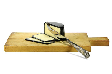 mature cheddar cheese with silver knife and cutting board isolated on white background