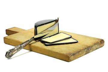 angeschnittener Cheddarkäse mit Silbermesser und Holzbrettchen isoliert auf weißem Hintergrund