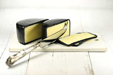 mature cheddar cheese with silver knife and ceramic cutting board isolated on wooden background