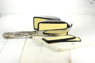 angeschnittener Cheddarkäse mit Silbermesser und Keramikbrettchen auf Holztisch