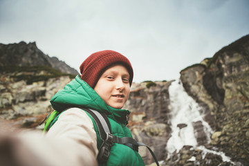 Boy mountain hiker invite somebody walk with him to waterfall
