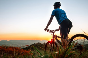 Man biker man meets a sunset in top of hill over the city