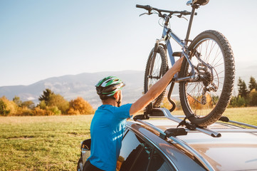 Mountain biker man take of his bike from the car roof