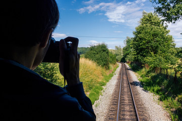 Photographer taking picture of train rails