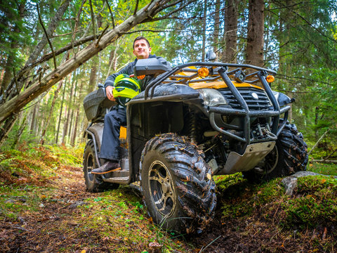 A man travels through the woods on the ATV. A man sits on the ATV in the forest. Off-road. A man travels on a quad.