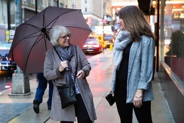 Two women walking and talking under umbrella on a rainy sidewalk in New York