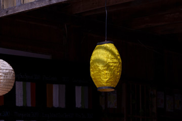 Yellow paper lantern in Chinese style, outdoor decor. Yellow paper lamp on dark background. Rustic handmade decoration