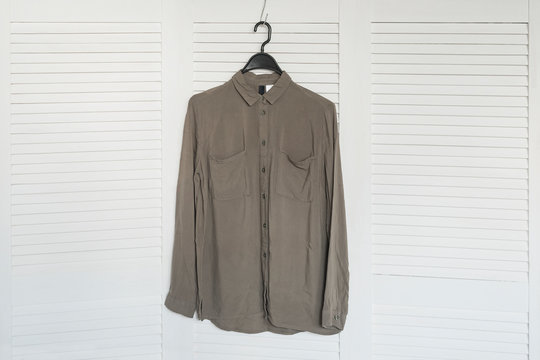 Khaki shirt hanging on a hanger. White wooden screen on the background. Fashionable wardrobe