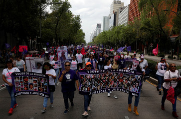 Demonstrators and relatives of women who were either murdered or disappeared hold crosses and banners with pictures of their relatives as they take part in a march for the Elimination of Violence Against Women in Mexico City