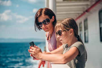 Mother and daughter traveling on ferry and taking pictures