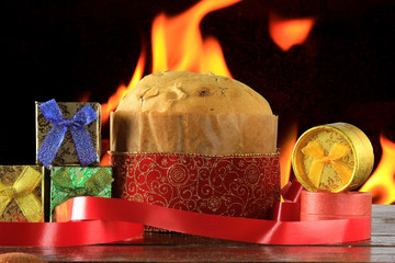 panettone, decorative christmas food, on wooden table, fire background