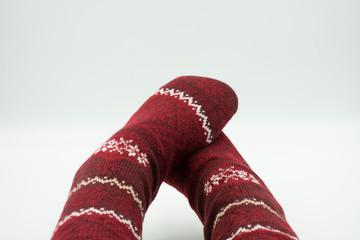 Füße in gemütlichen Weihnachtssocken isoliert auf weiß