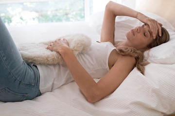 Young woman on bed with hot water bottle and hand on head