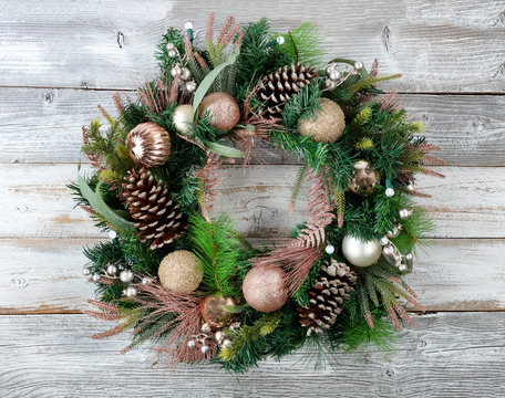Christmas holiday wreath with illuminated lights on rustic white wood