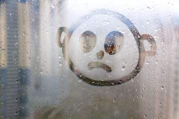 Foggy glass on window with drawn sad face concept photo with copyspace