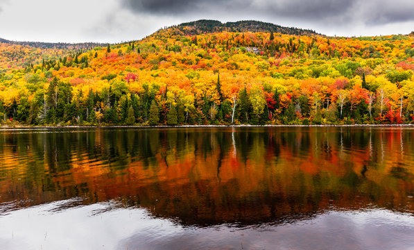 Fall colors of Lac Legault with Mont Kaaikop in the background, in cottage country in the Laurentians, Quebec, Canada.