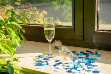 Ein Sektgläser mit Sekt und ein zweites Glas liegend auf der Fensterbank mit blauem Konfetti