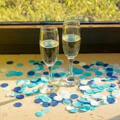 Zwei Sektgläser mit Sekt auf der Fensterbank bei Sonnenschein mit blauem Konfetti