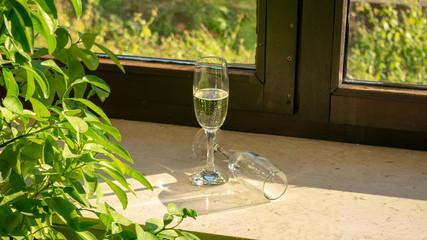 Ein Sektgläser mit Sekt und ein zweites Glas liegend auf der Fensterbank bei Sonnenschein