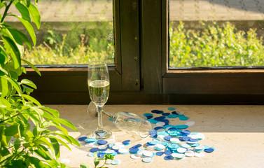 Sektgläser auf der Fensterbank bei Sonnenlicht mit blauem Konfetti