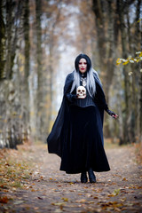 Image of witch girl in full growth in black cloak with skull