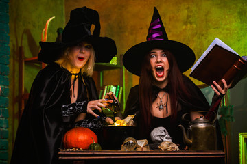 Image of two smiling two witches in black hats reading book of incantations