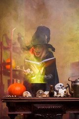 Image of witch with pumpkin and spell book at table
