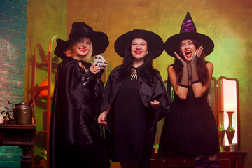 Picture of three witches in black hats in dark room against mirror and rack