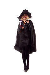 Full-length photo of witch blonde in black hat with book of spells