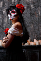 Photo of zombie woman with white face and red flower on her head