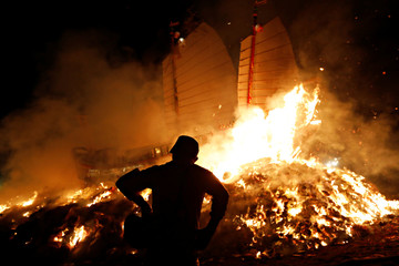 A participant reacts as the 'Wang Yeh's Boat', a 13-meter finely crafted ancient warship made of paper and wood setting on fire to ward off evil, disease and bad luck during Wang Yeh Boat Burning Festival, in Pingtung
