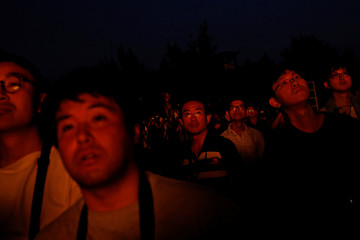 Onlookers react as the 'Wang Yeh's Boat', a 13-meter finely crafted ancient warship made of paper and wood setting on fire to ward off evil, disease and bad luck during Wang Yeh Boat Burning Festival, in Pingtung