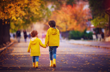 two happy kids, brothers walking together on autumn street in yellow raincoats and rubber boots