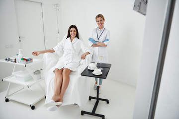 Full length portrait of attractive woman with intravenous drip lying on deckchair while physician crossing arms. They looking at camera and smiling